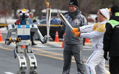 Dennis Hong ignites the torch of the first Olympic relay robot
