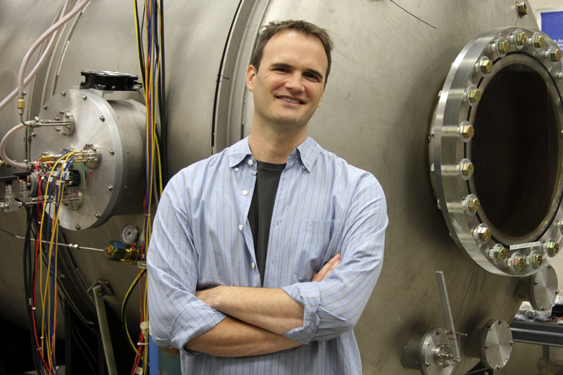 Richard Wirz standing in front of a large vacuum chamber used to test high-power electric propulsion systems.