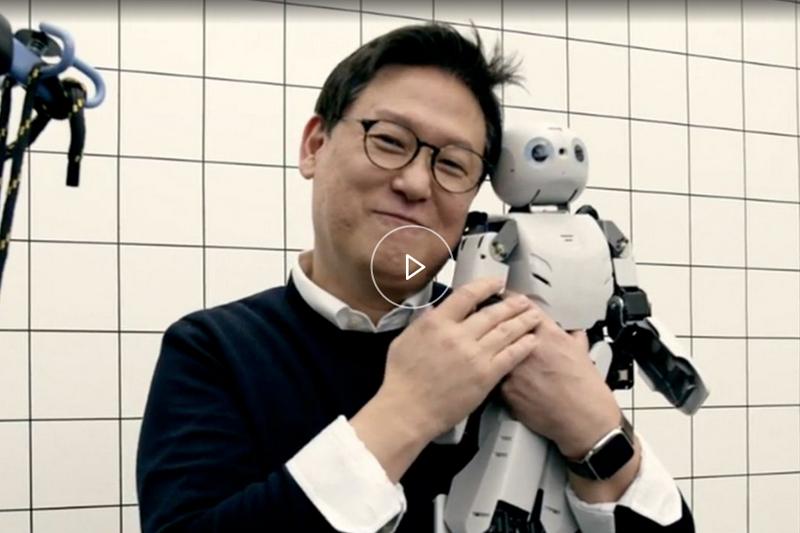 Dennis Hong holding small robot